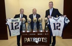 Robert Kraft (au centre), propriétaire des New England Patriots, se fait remettre les maillots de Tom Brady par des agents du FBI.