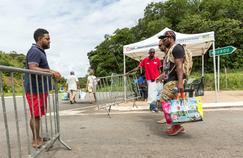 Les bras chargés, des habitants franchissent un barrage routier près de Kourou, en Guyane.