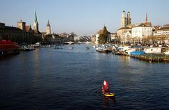 Un homme déguisé en Père Noël traverse la rivière Limmat, qui traverse Zurich, en paddle.