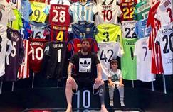 Lionel Messi et son enfant posent devant la collection privée de maillot du joueur argentin.