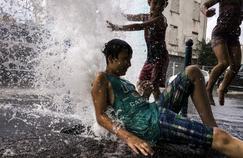Des enfants s'amusent près d'une bouche d'incendie, mercredi 21 juin.