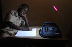 Un enfant faisant ses devoirs à la lueur de Solarpark.