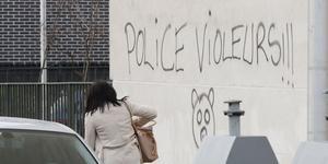 Une femme passe devant un graffiti laissé sur un mur d'Aulnay-sous-Bois, lundi. Des incidents ont éclaté dans la nuit, pour le deuxième soir consécutif.