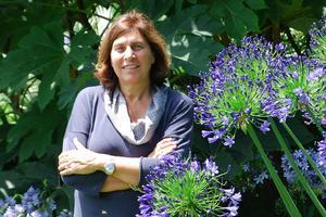 Silvia Ricci pose entre des fleurs d'agapanthe et les feuilles d'un <i>Tetrapanax papyrifer</i>.