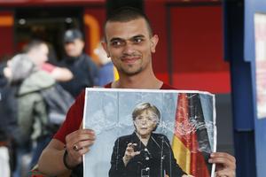 Un réfugié tient entre ses mains une photo d'Angela merkel à la gare de Munich, le 5 septembre 2015