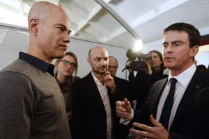 Manuel Valls parle avec le journaliste Laurent Léger, à gauche, le 9 janvier 2015, dans les locaux de <i>Libération</i>, qui a accueilli la rédaction de <i>Charlie Hebdo </i>après les attentats.