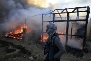 Un migrant à côté d'un abri en flammes.