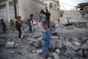 Les enfants continuent de jouer sur les ruines d'une maison détruite par les frappes aériennes.