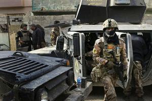 À Mossoul, dans le secteur Saddam, des hommes des forces antiterroristes irakiennes de l'I.C.T.F. entrent dans certaines maisons pour sécuriser le quartier et permettre la progression des troupes, le 10 novembre.