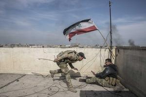 Sous le feu ennemi, lundi, deux hommes des forces spéciales de la police accrochent le drapeau irakien sur le toit d'un hôtel repris aux djihadistes. Dans la précipitation, ils n'ont pas réalisé que le drapeau flottait à l'envers.