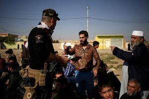À un checkpoint à l'est de Mossoul, un soldat des forces spéciales irakiennes contrôle l'identidé des habitants.