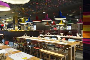 Le restaurant du RockyPop Hotel propose une salle style réfectoireavec de grandes tablées.