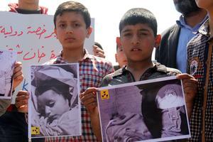 Des manifestants brandissent les photos des victimes de l'attaque chimique, le 7 avril.