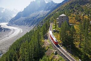 Petit train rouge à crémaillère menant à l'hotel refuge de Montenvers, fondant le paysage des montagnes de Chamonix.