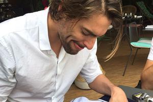 Camille Lacourt en train de signer une veste