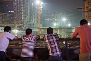 Des résidents fraîchement débarqués de leurs campagnes observent, fascinés, un gigantesque chantier de gratte-ciel en construction dans le sud-ouest de la Chine.