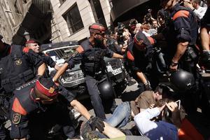 Des officiers de la police régionale catalane tentent de disperser des manifestants postés devant le siège des Affaires étrangères de Catalogne, le 20 septembre 2017 à Barcelone.