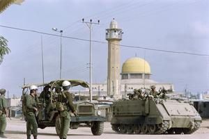 Les soldats israéliens passent devant une mosquée du camp de réfugiés de Jabalia dans la bande de Gaza, le 9 décembre 1987.