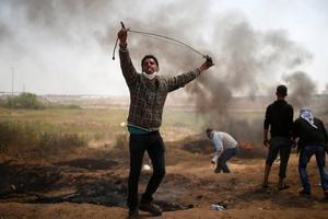 Les manifestants Palestiniens jettent des pierres en direction des soldats israéliens