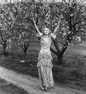 Une jeune femme se réjouit des arbres en fleur.