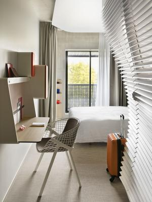Un lit double, un petit écran plat, deux boxes orange, l'une pour la bouteille d'eau, l'autre pour la machine Nespresso, résument avec un petit bureau un aménagement efficace mais sans fantaisie.