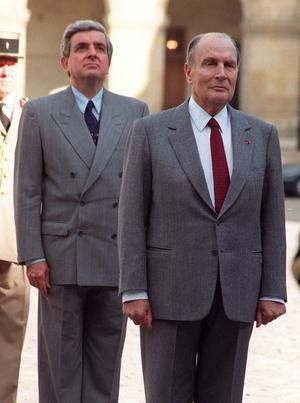 Jean-Pierre Chevènement, alors ministre de la Défense, derrière le président François Mitterrand lors d'une prise d'armes aux Invalides à Paris, le 5 octobre 1990.