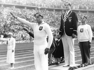 Sur le podium du 100 mètres canoë, Erich Koschik, médaille de bronze, fait le salut hitlérien.