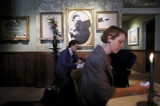 Clients assis dans une salle du «Walled Off Hotel», décoré par Banksy
