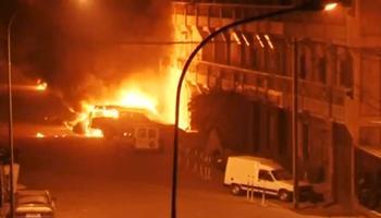 Des voitures en feu devant l'hôtel où les assaillants étaient encore retranchés aux premières heures du jour, samedi matin.