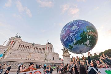 Des Italiens jouent avec un immense ballon représentant la Terre, lors d'un rassemblement pour le climat, dimanche, sur la Piazza Venezia, à Rome.