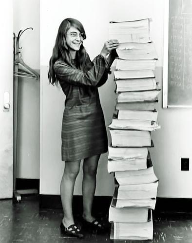 Margaret Hamilton, posant à côté du code informatique qu'elle a rédigé.