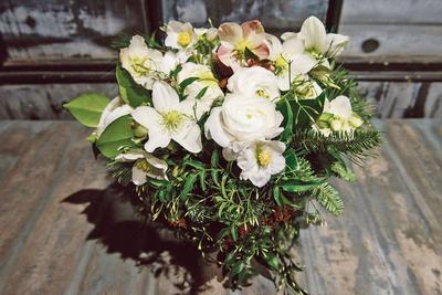 Bouquet d'hellébores associé à des renoncules, des lianes de jasmin et quelques branches de pin. DR