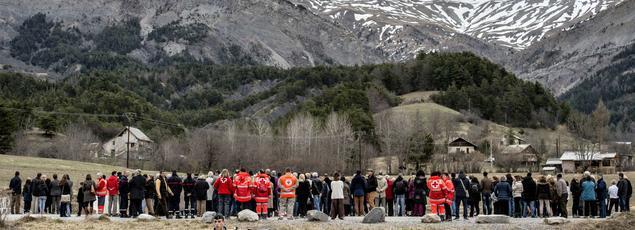 Des habitants de Seyne-les-Alpes et des membres de la Croix-Rouge rendent hommage aux victimes du crash lors d'un rassemblement à Le Vernet, samedi.
