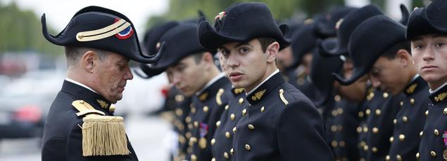 Un chef de détachement ajuste l'uniforme d'un étudiant de Polytechnique avant le défilé militaire du 14 juillet 2014.