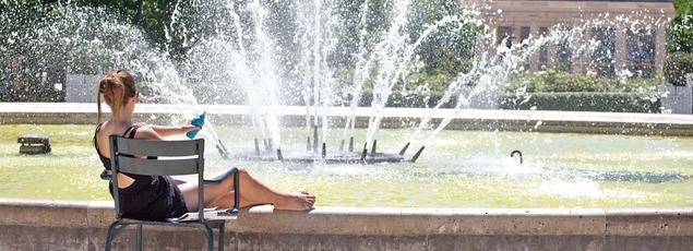 Une jeune femme se protège avec de la crème solaire devant une fontaine dans les jardin du Palais Royal, à Paris, le 30 juin.