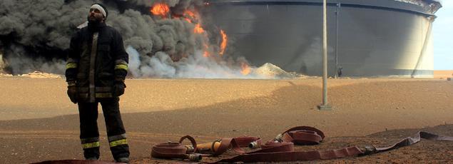 Un pompier libyen devant un réservoir en feu sur le centre de raffinage de Ras Lanouf après une offensive menée, la semaine dernière, par les militants de Daech en vue de s'emparer des installations portuaires et pétrolières.