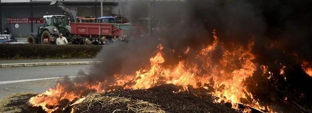 Des agriculteurs ont brulé de la paille et des pneus ce jeudi devant une grande surface à Dol de Bretagne. (Crédit photo AFP/Damien Meyer).