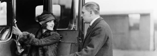 Un homme prévenant tient la portière pour permettre à une jeune femme de monter, vers 1920.