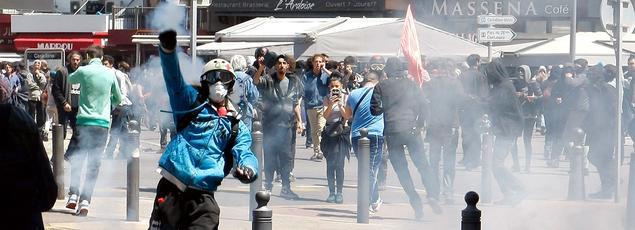 Un manifestant protégé d'un casque lance des projectile sur des CRS.