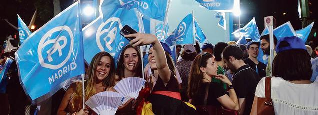 Des militants fêtent la victoire de Mariano Rajoy devant le quartier général du Parti Populaire, dimanche, à Madrid.