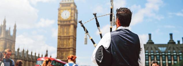Un homme en costume traditionnel écossais joue de la cornemuse devant Big Ben le 26 juin 2016.