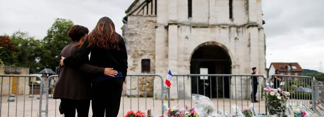 Deux passantes se recueillent devant l'église sous surveillance de Saint-Étienne-du-Rouvray, où le prêtre Jacques Hamel a été égorgé mardi.
