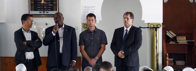 Le Père Auguste Moanda, curé de la paroisse de Saint-Etienne-du-Rouvray (deuxième en partant de la gauche), dans la mosquée de la ville, le 29 juillet. A l'extrême-droite, Anouar Kbibech, président du Conseil français du culte musulman.