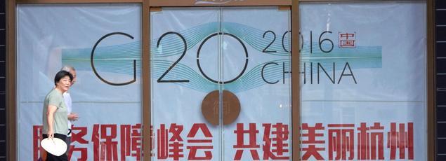 Un couple de Chinois passe devant une affiche annonçant le prochain sommet du G20, qui se tiendra à Hangzhou, dans la province de Zhejiang, les 4 et 5septembre.