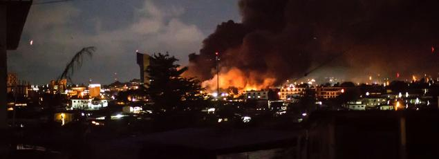 Des flammes s'élèvent dans un quartier de Libreville, mercredi soir.
