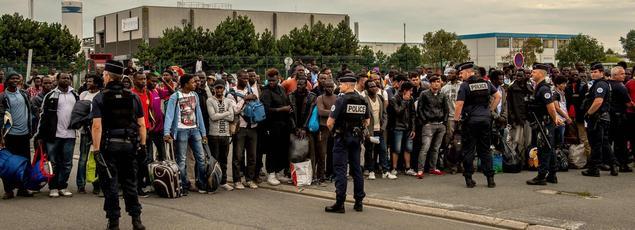 Sous le contrôle des forces de police, des réfugiés de Calais attendent des bus avant d'être réinstallés dans des centres d'hébergement.