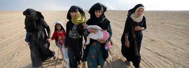 Au sud de Mossoul, jeudi, ces femmes et ces enfants marchent vers le village d'où ils avaient fui il y a plusieurs mois pour échapper aux djihadistes de Daech.