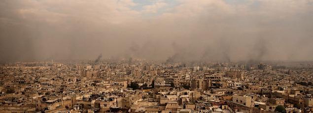 Vue d'Alep, sous un nuage de fumée, après les pilonnages, mercredi, de quartiers de la vieille ville.
