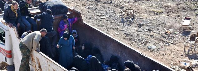Des civils ayant réussi à fuir dans un camion arrivent à un check-point tenu par les forces gouvernementales, vendredi dans les faubourgs d'Alep.