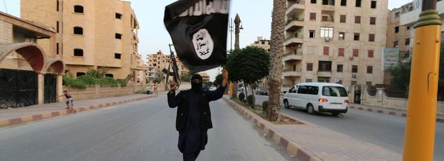 Un djihadiste portant le drapeau de l'Etat islamique, le 29 juin 2014 à Raqqa (Irak).